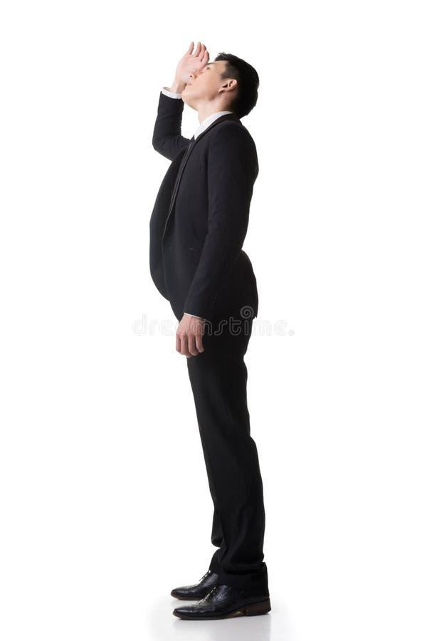 O suporte asiático do homem de negócio e olha acima fotos de stock