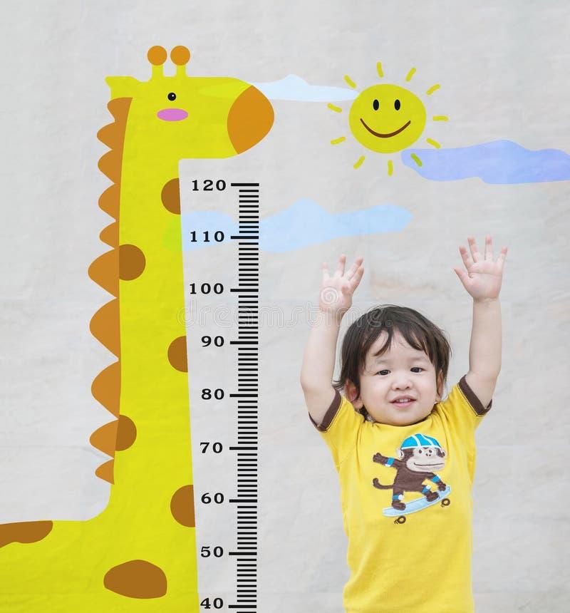 O suporte asiático feliz da criança do close up para a medida da altura com desenhos animados bonitos na parede de pedra de mármo foto de stock royalty free