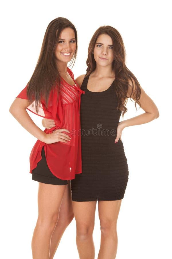 O suporte de duas mulheres nos vestidos fecha-se junto fotografia de stock royalty free