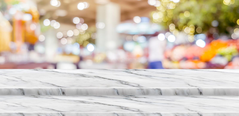 O suporte de mármore branco do alimento do tampo da mesa da etapa vazia com o bokeh do fundo do supermercado do borrão claro, zom imagens de stock