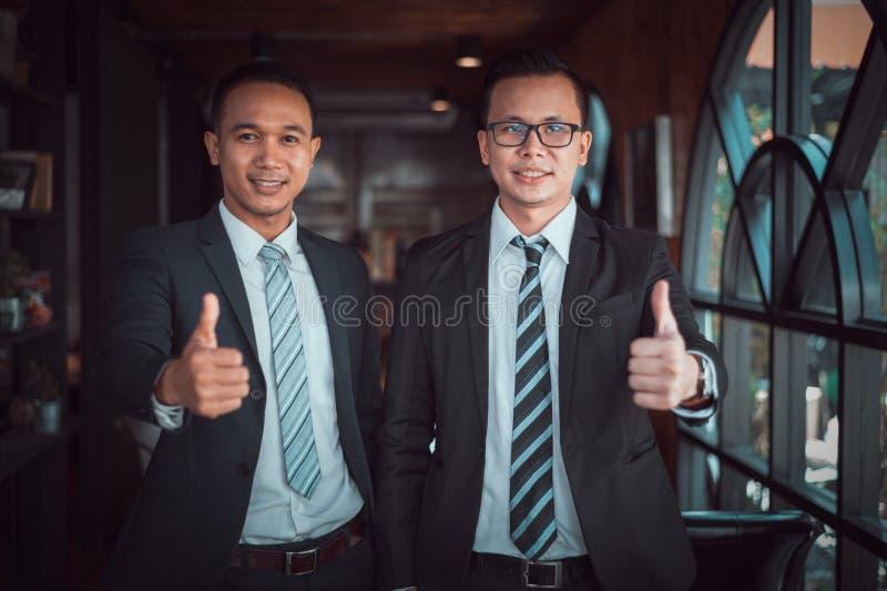 O suporte do homem de negócios de dois asiáticos e o sorriso e a mostra manuseiam acima no escritório foto de stock royalty free