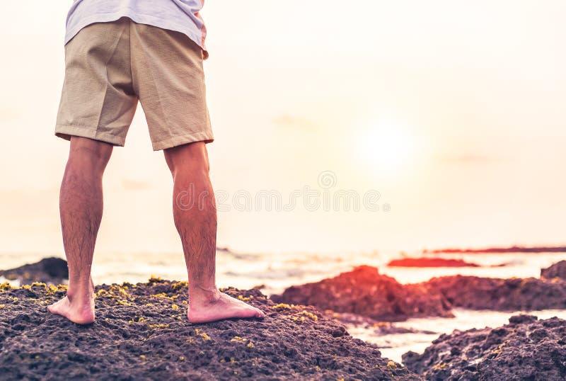 O suporte do homem na rocha imagens de stock royalty free
