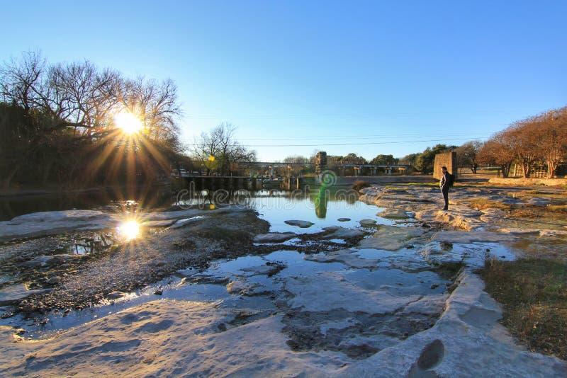 O suporte do homem sozinho na rocha no por do sol Sun e as pedras são refletidos na água com céu azul imagem de stock royalty free