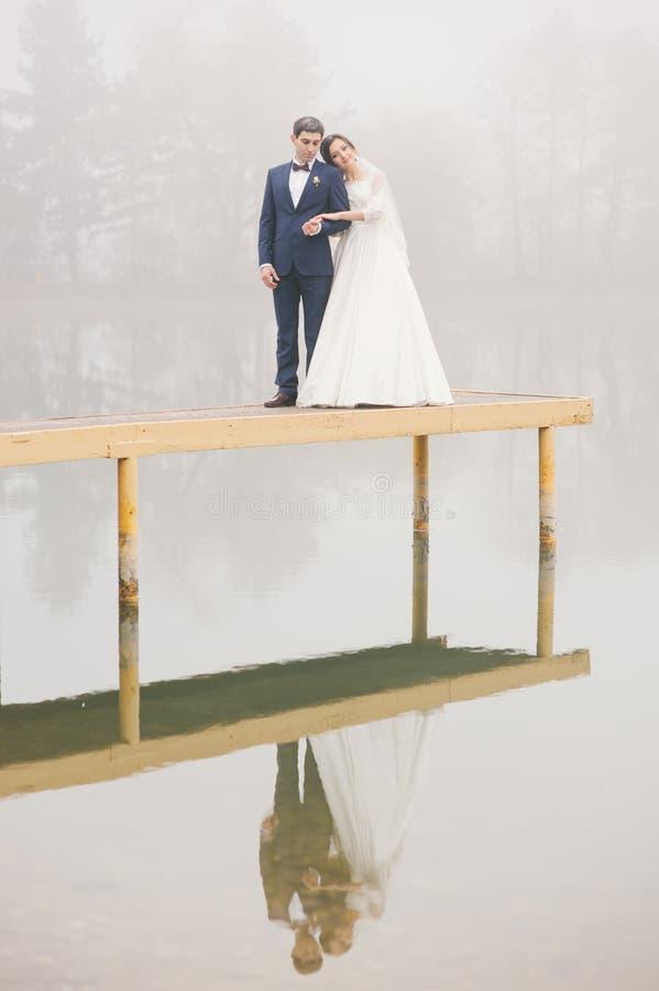 O suporte do noivo e da noiva no cais é refletido na água fotos de stock royalty free