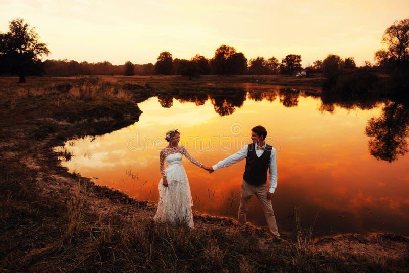 O suporte dos noivos pelo lago, após a cerimônia de casamento Os recém-casados estão sorrindo Foto mostrada em silhueta na matiza imagem de stock