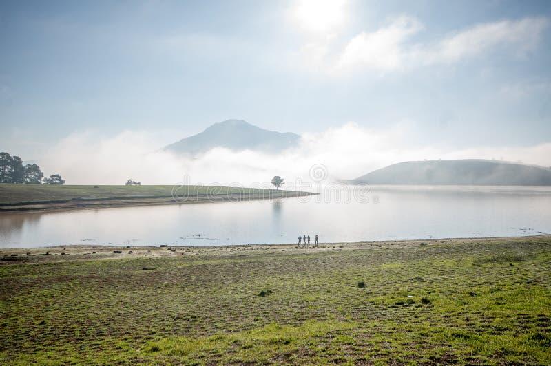 O suporte pela árvore sozinha do anh do lago no lago, nascer do sol no mountai, nevoento, nuvem do homem no céu imagens de stock royalty free
