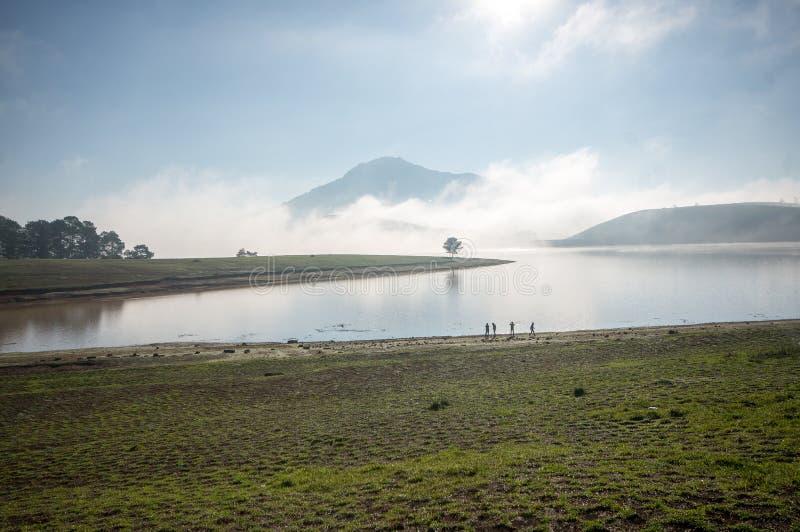 O suporte pela árvore sozinha do anh do lago no lago, nascer do sol no mountai, nevoento, nuvem do homem no céu fotos de stock