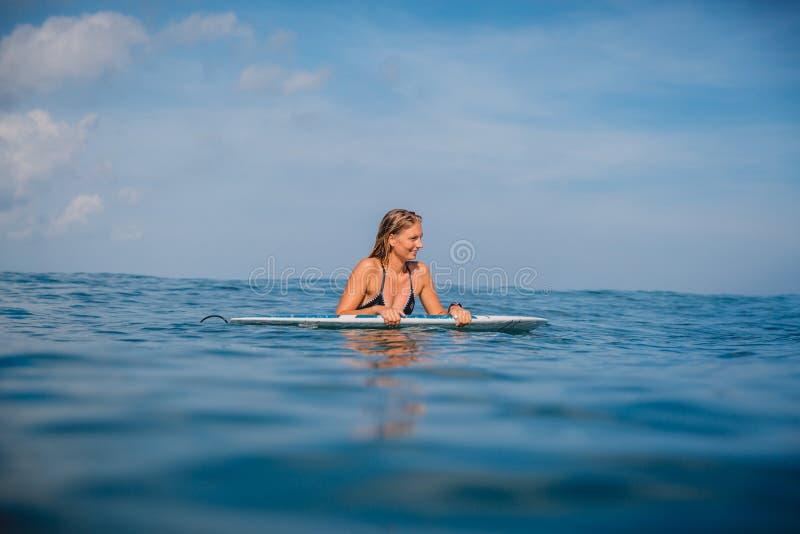 O surfgirl bonito relaxou com prancha e observação em ondas Surfista com prancha imagem de stock royalty free