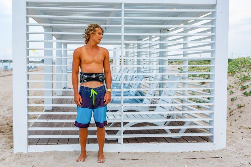 O surfista attceractive novo do indivíduo está na praia que olha para fora na distância, fotografia de stock