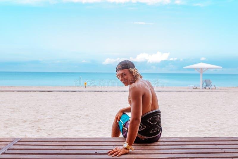 O surfista senta-se no terraço na praia com o o seu de volta à câmera e gerencie-se a cara que olha para a câmera fotos de stock royalty free