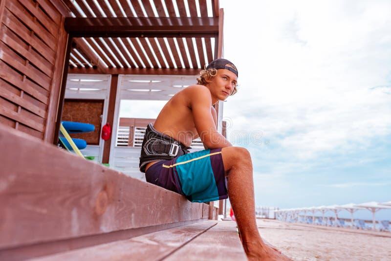 O surfista senta-se no terraço na praia e na vista à câmera Vista lateral foto de stock