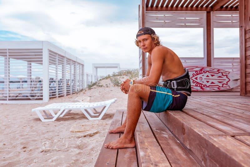 O surfista senta-se no terraço na praia e na vista à câmera Vista lateral fotos de stock royalty free