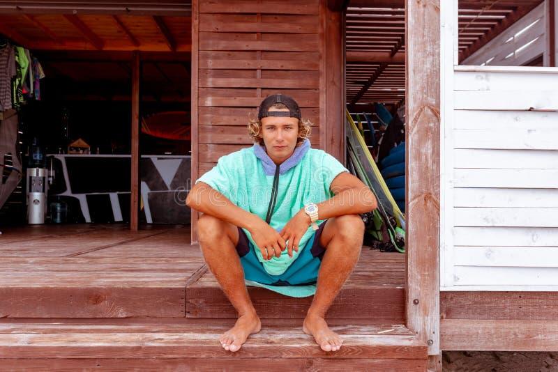O surfista senta-se no terraço na praia que olha para fora na câmera imagem de stock