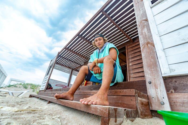 O surfista senta-se no terraço na praia que olha para fora na distância imagem de stock royalty free