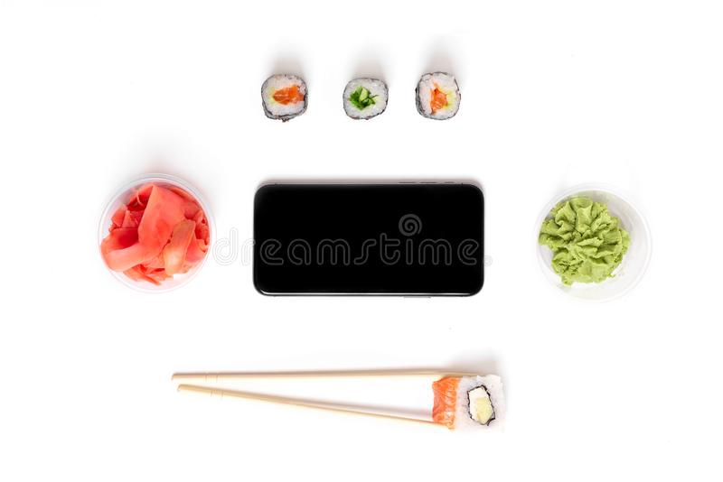 O sushi ajustou rolos no conceito branco do alimento da entrega do telefone do gengibre do wasabi dos hashis do fundo foto de stock royalty free