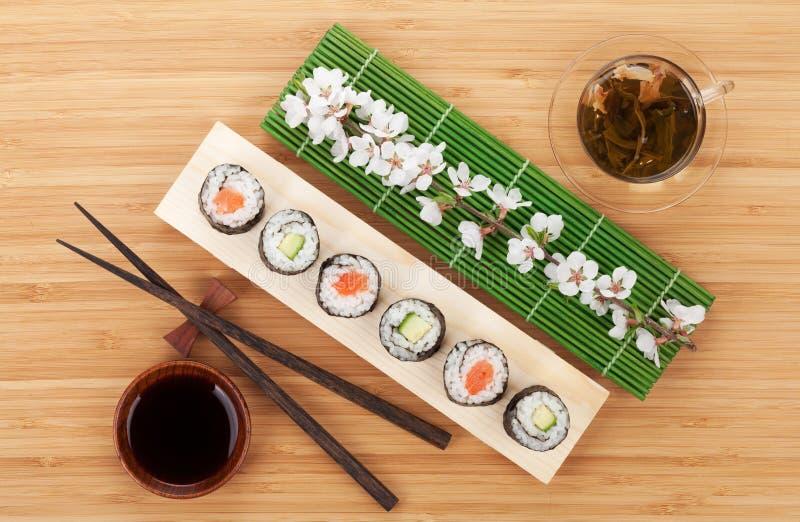 O sushi ajustou-se com chá verde e ramo de sakura foto de stock