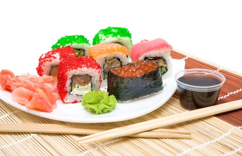 O sushi com caviar vermelho e os rolos fecham-se acima em uma placa branca imagem de stock