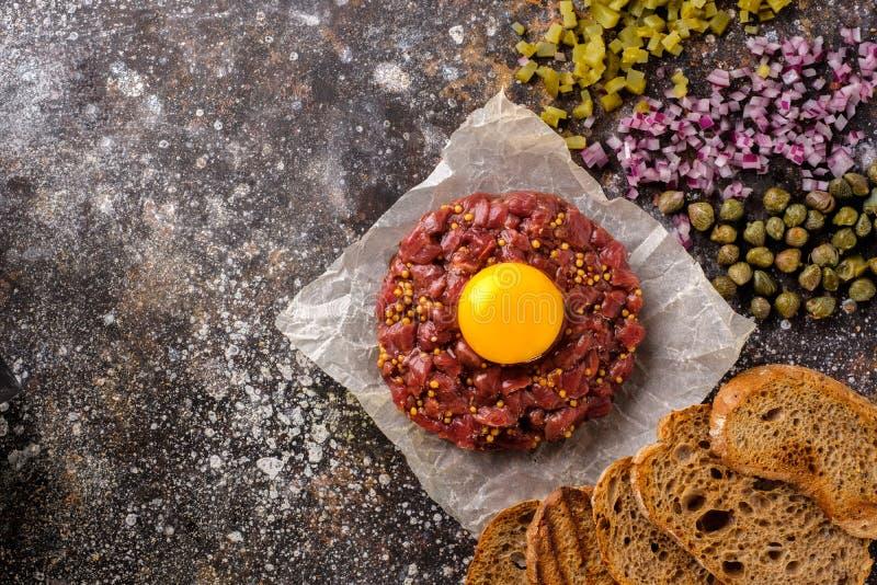 O tártaro fresco da carne é servido com gema, pão fritado, cucu conservado fotografia de stock