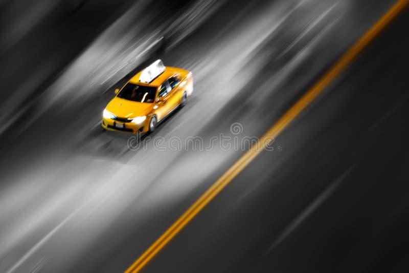 O táxi amarelo de Nova York em movimento, correndo pela rua em um fundo desfocado imagem de stock royalty free