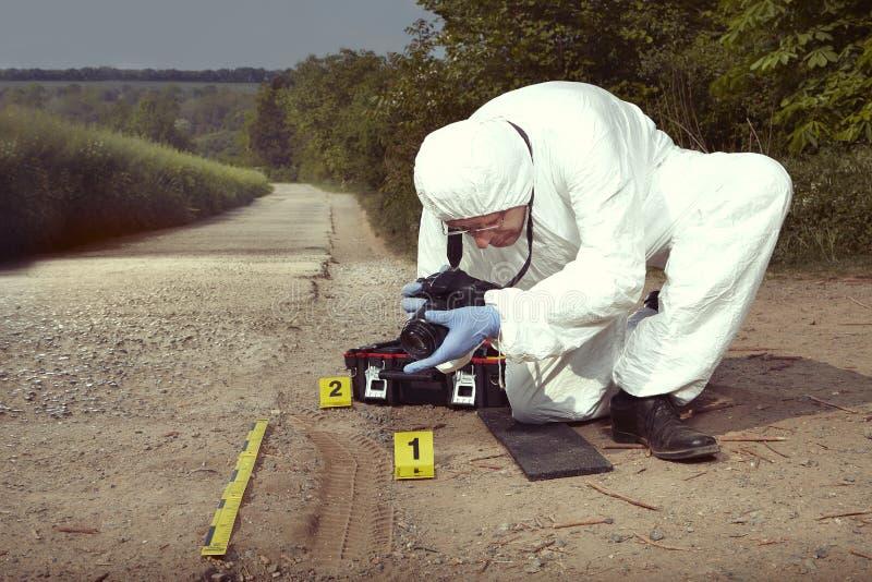 O técnico Criminologist que fotografa a cópia do pneu saiu na poeira da maneira do campo fotografia de stock