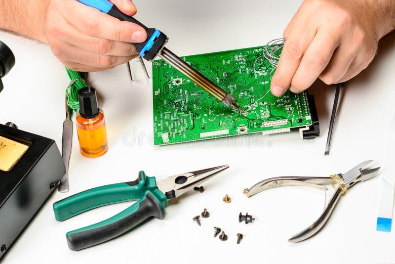O técnico da eletrônica substitui o elemento detrabalho do dispositivo eletrónico com um ferro de solda As mãos do fotografia de stock