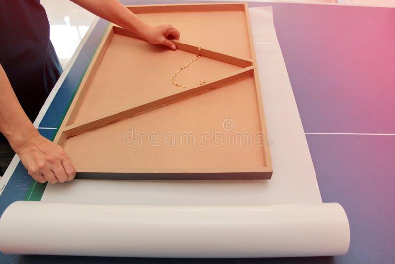 O técnico da fotografia está colocando o quadro flutuante sobre o adesivo de dois lados para unir o adesivo imagens de stock