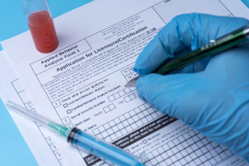 O técnico de laboratório escreve os resultados da análise no formulário fotos de stock