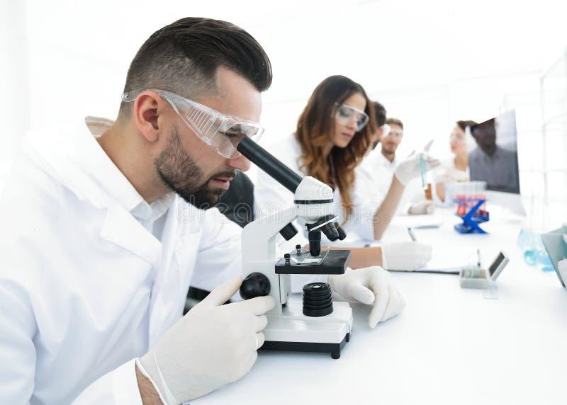 O técnico de laboratório masculino olha a amostra sob um microscópio imagem de stock royalty free