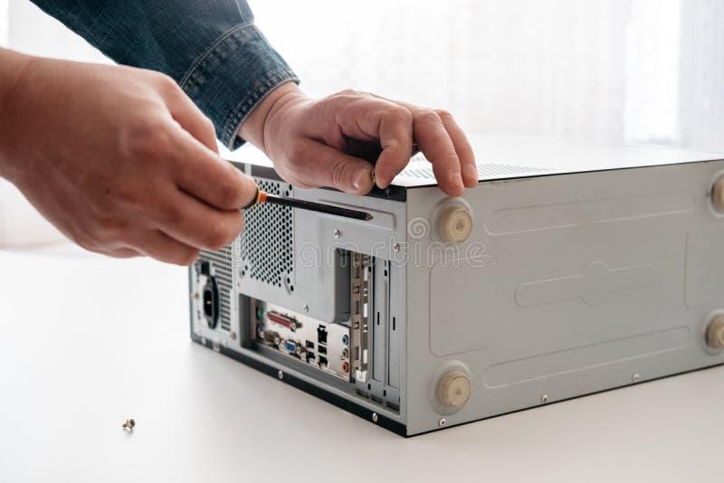 O técnico desmonta o computador com uma chave de fenda para o diagnóstico dos problemas foto de stock