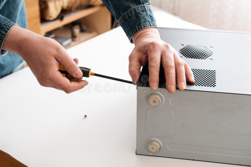 O técnico desmonta o computador com uma chave de fenda para o diagnóstico dos problemas imagens de stock royalty free