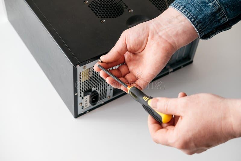 O técnico desmonta o computador com uma chave de fenda para o diagnóstico dos problemas imagens de stock