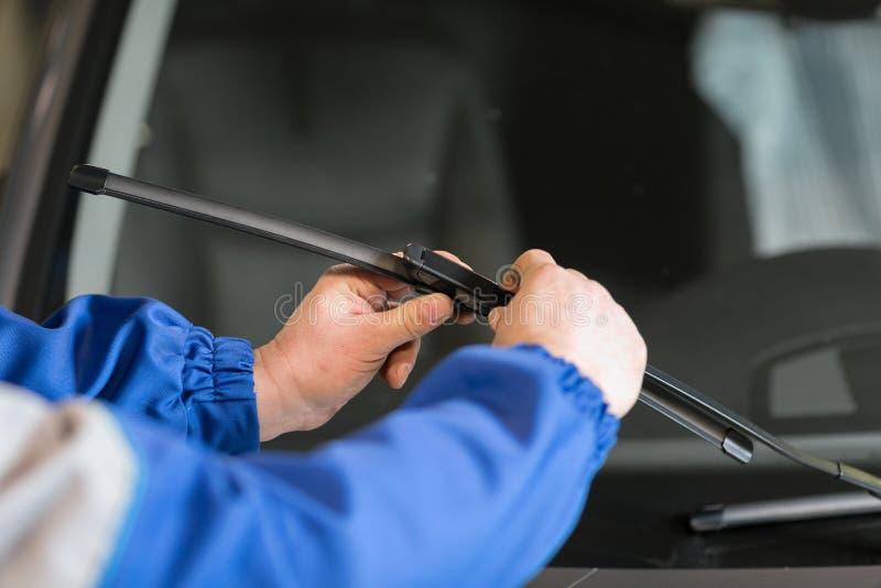 O técnico está mudando limpadores de pára-brisas em uma estação do carro imagem de stock