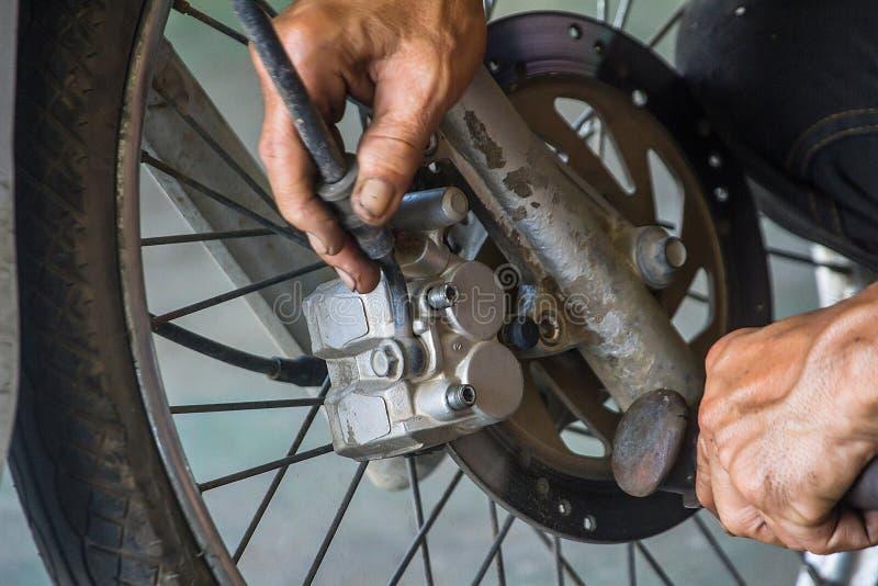O técnico está removendo a bomba do disco do ` s da motocicleta fotografia de stock