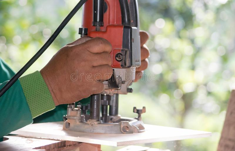 O técnico está usando uma máquina de perfuração de madeira fotos de stock