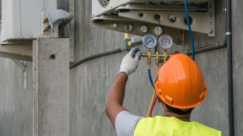 O técnico está verificando o condicionador de ar fotos de stock
