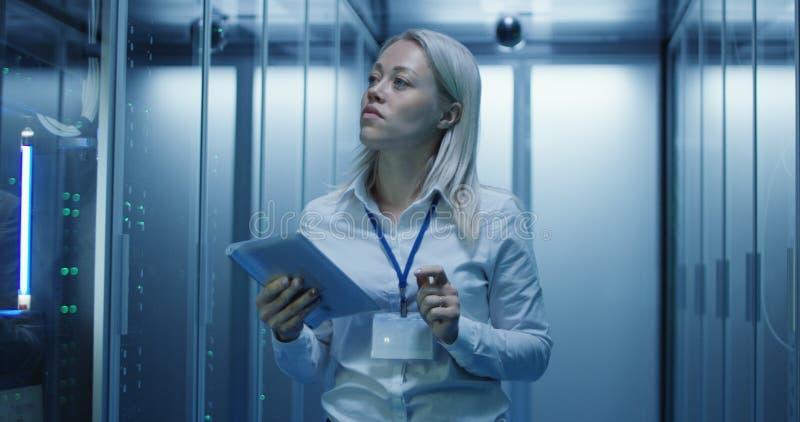 O técnico fêmea trabalha em uma tabuleta em um centro de dados imagens de stock royalty free