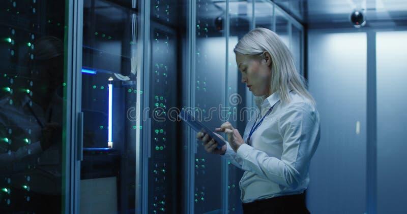 O técnico fêmea trabalha em uma tabuleta em um centro de dados imagem de stock royalty free