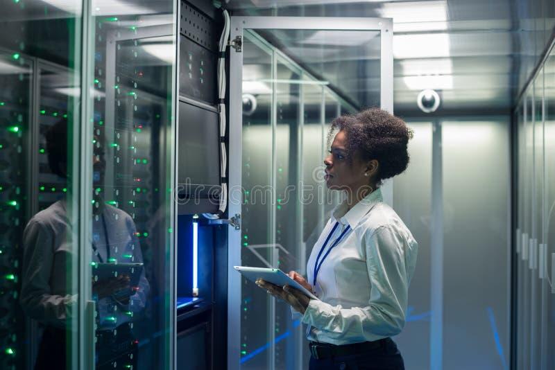 O técnico fêmea trabalha em uma tabuleta em um centro de dados fotografia de stock