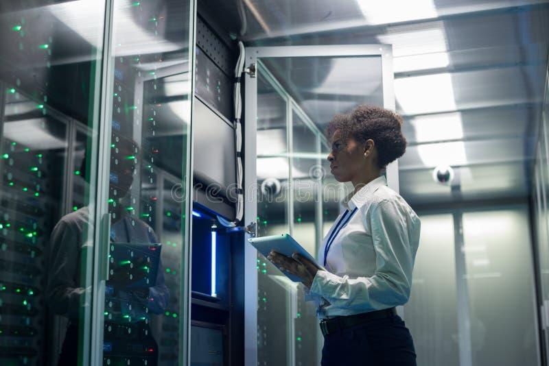 O técnico fêmea trabalha em uma tabuleta em um centro de dados imagens de stock