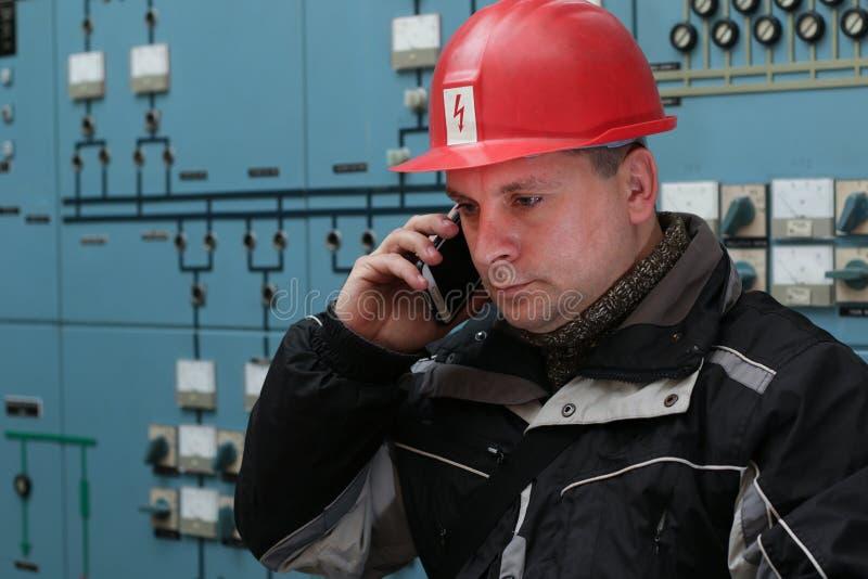 O técnico faz o telefonema no centro de controle do central elétrica fotos de stock