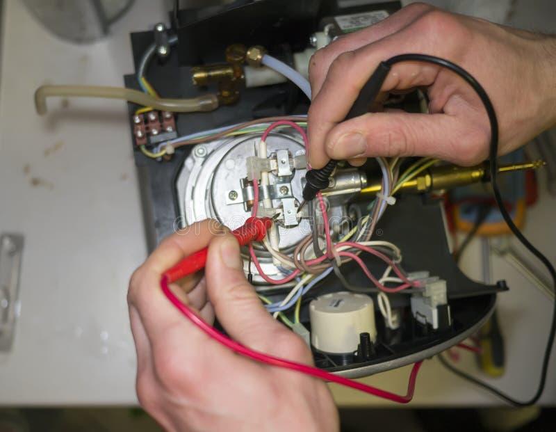 O técnico mede a resistência do sensor do coffeemachine imagem de stock