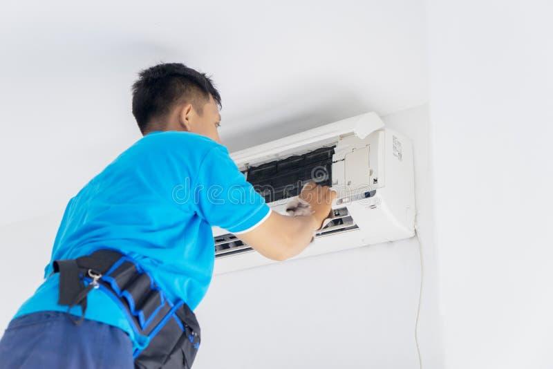 O técnico novo limpa o condicionador de ar com um pano fotografia de stock royalty free