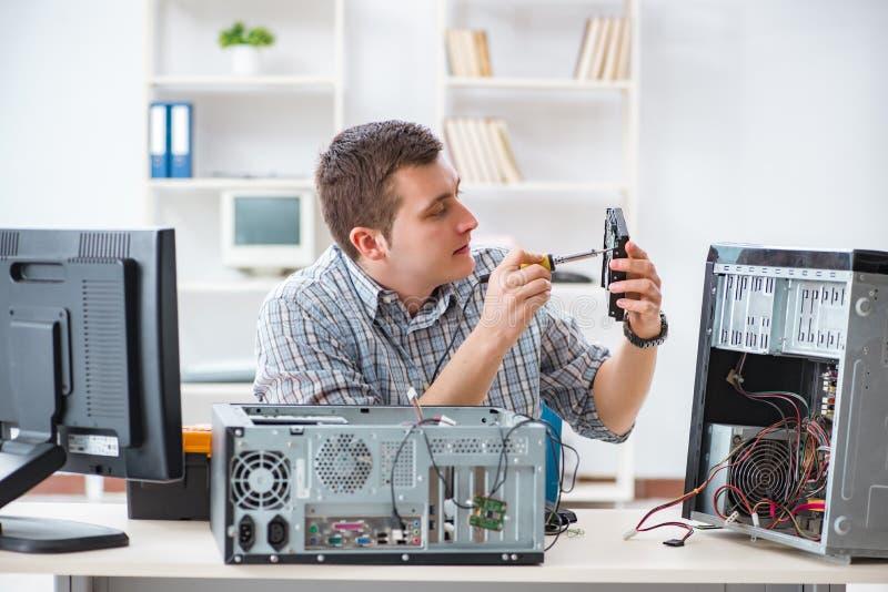 O técnico novo que repara o computador na oficina fotografia de stock