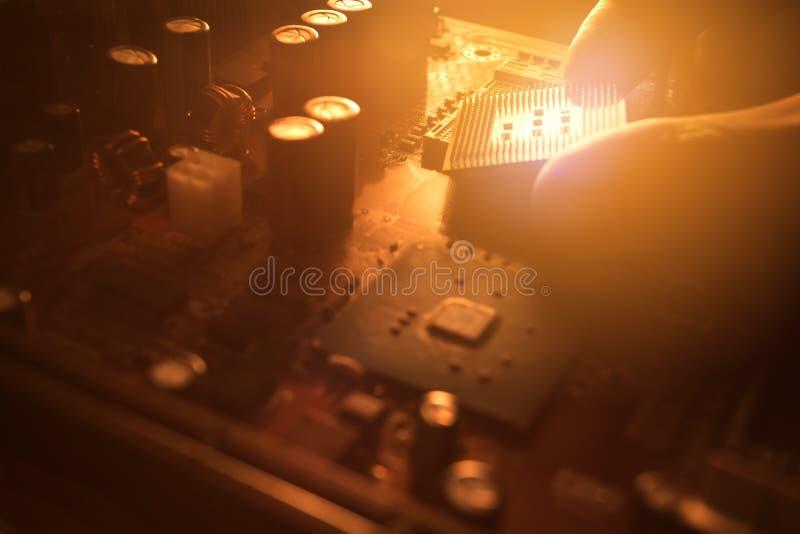 O técnico obstrui dentro o microprocessador do processador central ao cartão-matriz fotos de stock royalty free