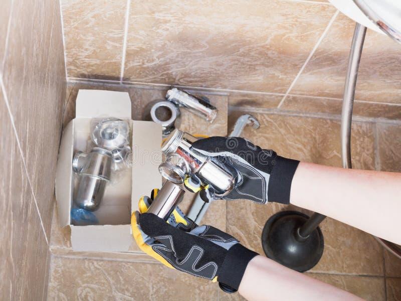 O técnico sanitário substitui a armadilha do encanamento do dissipador foto de stock royalty free