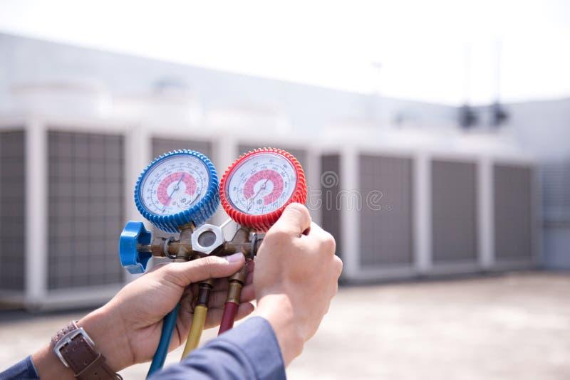 O t?cnico est? verificando o condicionador de ar, equipamento de medi??o para condicionadores de ar de enchimento imagens de stock