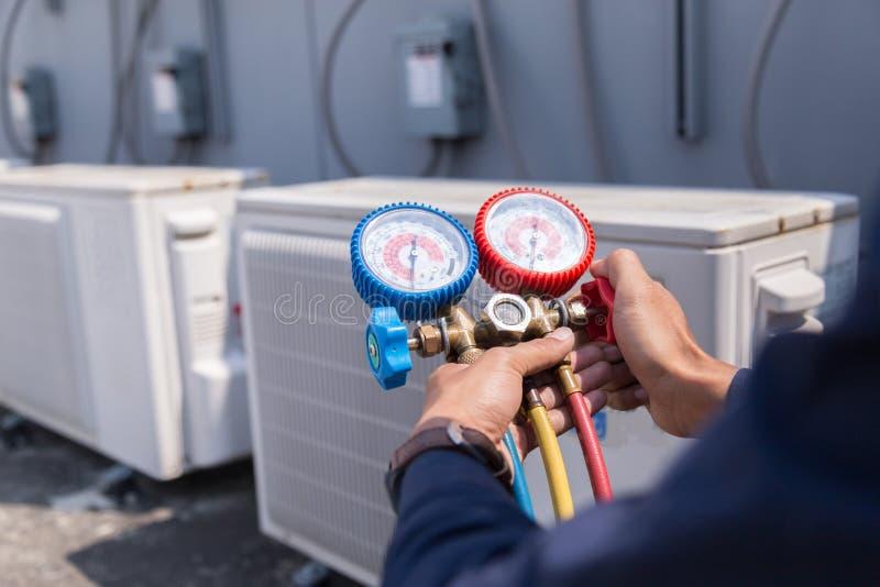 O t?cnico est? verificando o condicionador de ar, equipamento de medi??o para condicionadores de ar de enchimento imagem de stock