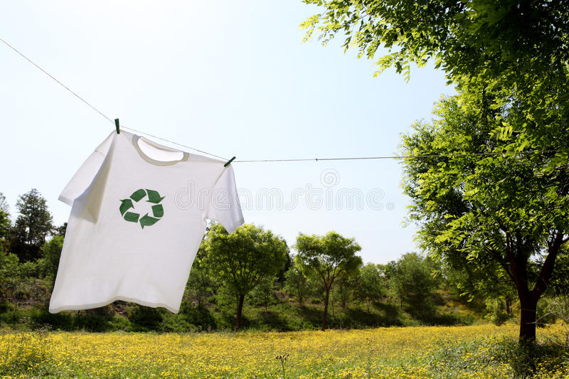 O t-shirt com recicl a secagem do logotipo no clothesline foto de stock