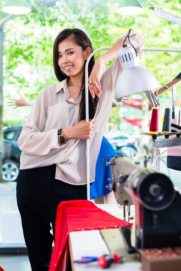 O tainlor ou o desenhador de moda asiático inclinam-se na mesa da costura imagem de stock