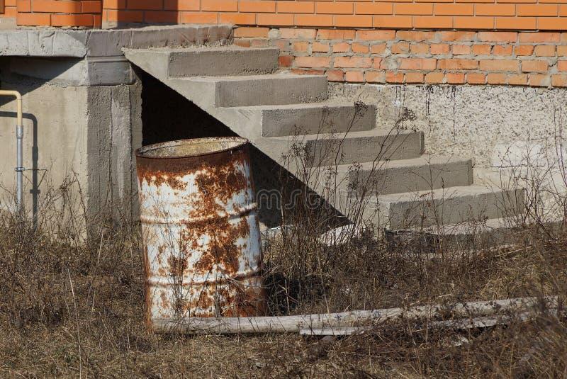 O tambor velho oxidado está na grama seca perto da casa com uma escada imagem de stock